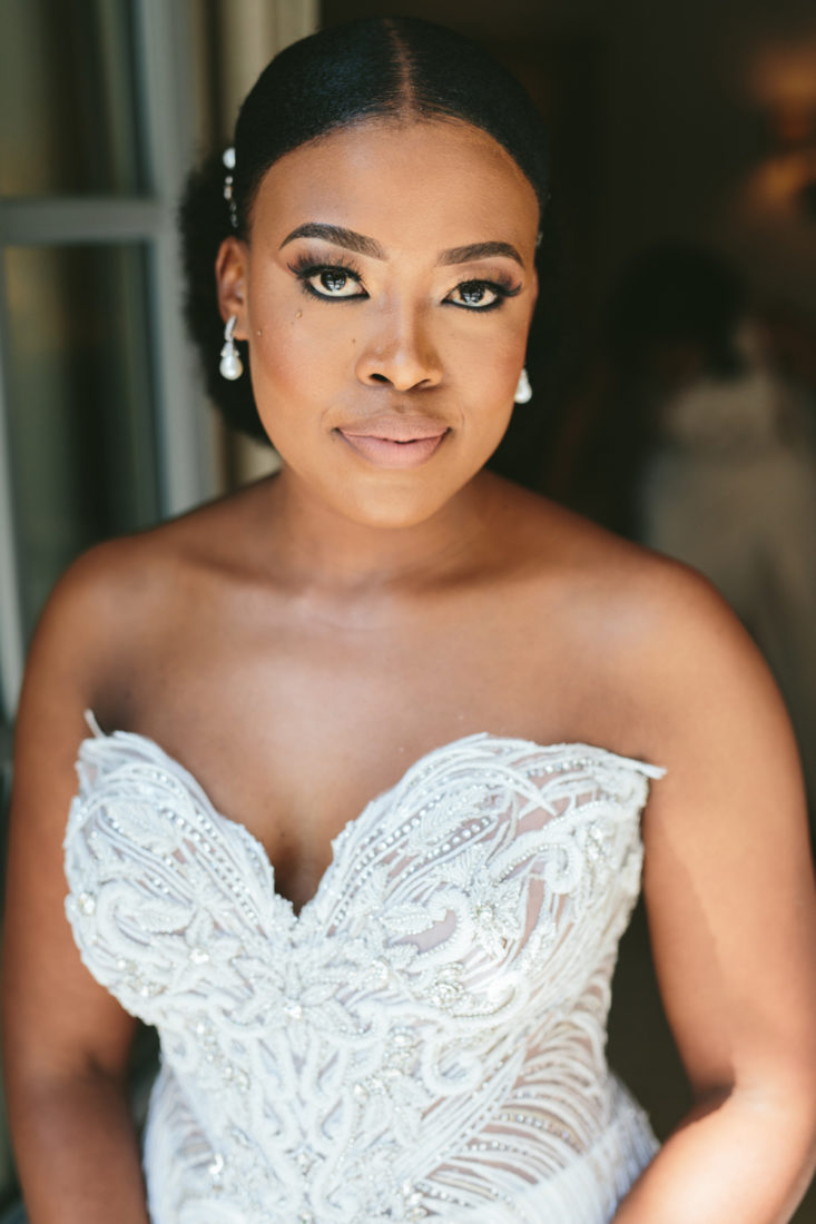 a portrait photo of a bride wearing a white beaded dress and pearl earrings.