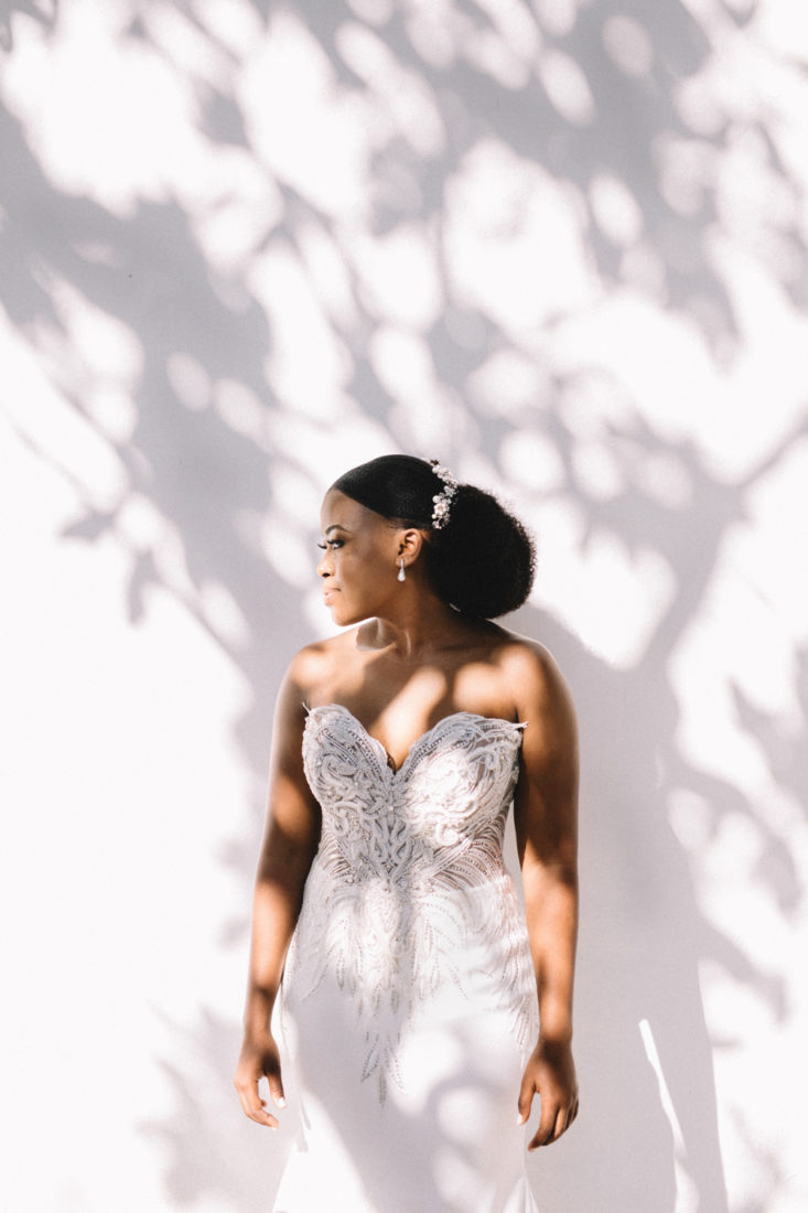 a bride wearing a tight fitted white beaded dress and pearl earrings with sunlight hitting het through the trees.