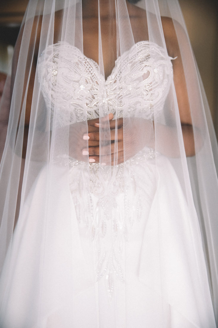 a close up image of a white beaded wedding dress and a veil covering her.