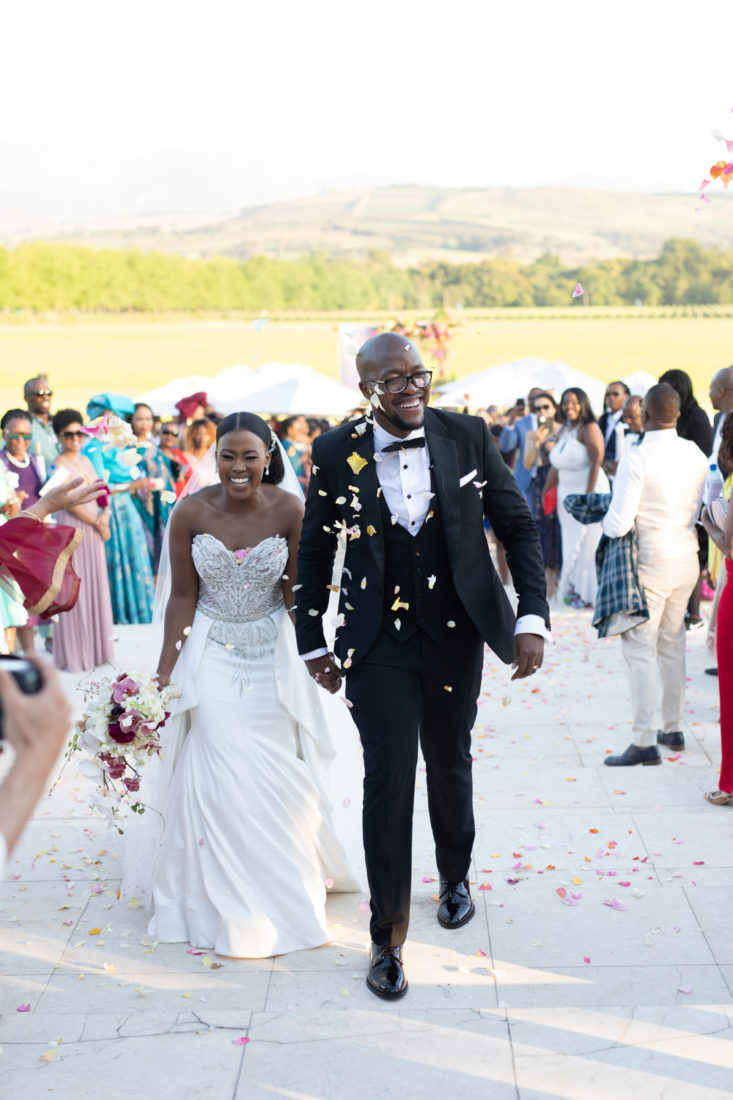 a bride and groom getting thrown with rose petals as they walk up the stairs at the Laurent venue Lourensford.