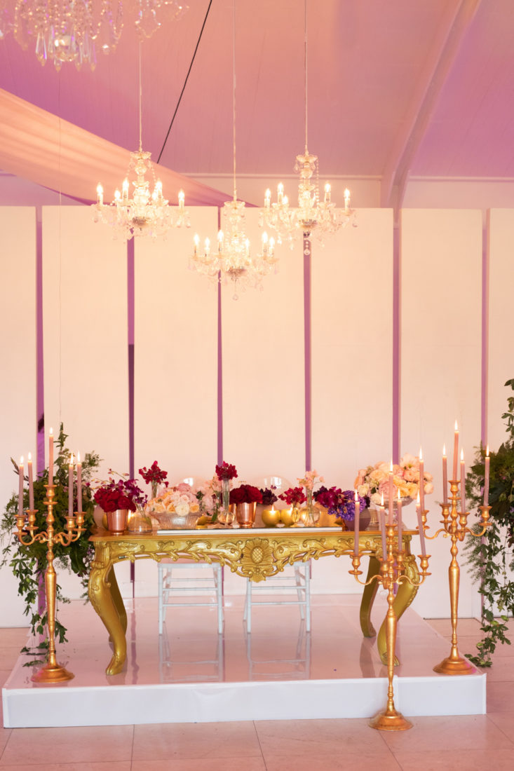 a bridal table at Laurent venue, with a golden table with big candleholders and pink floral arraignments.