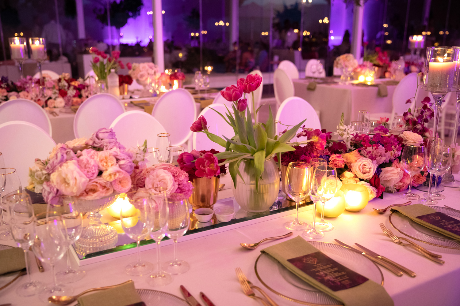 a decor shot in Laurent venue of pink floral arraignments on a mirror with gold cutlery and a golden rim under plate and white chairs.