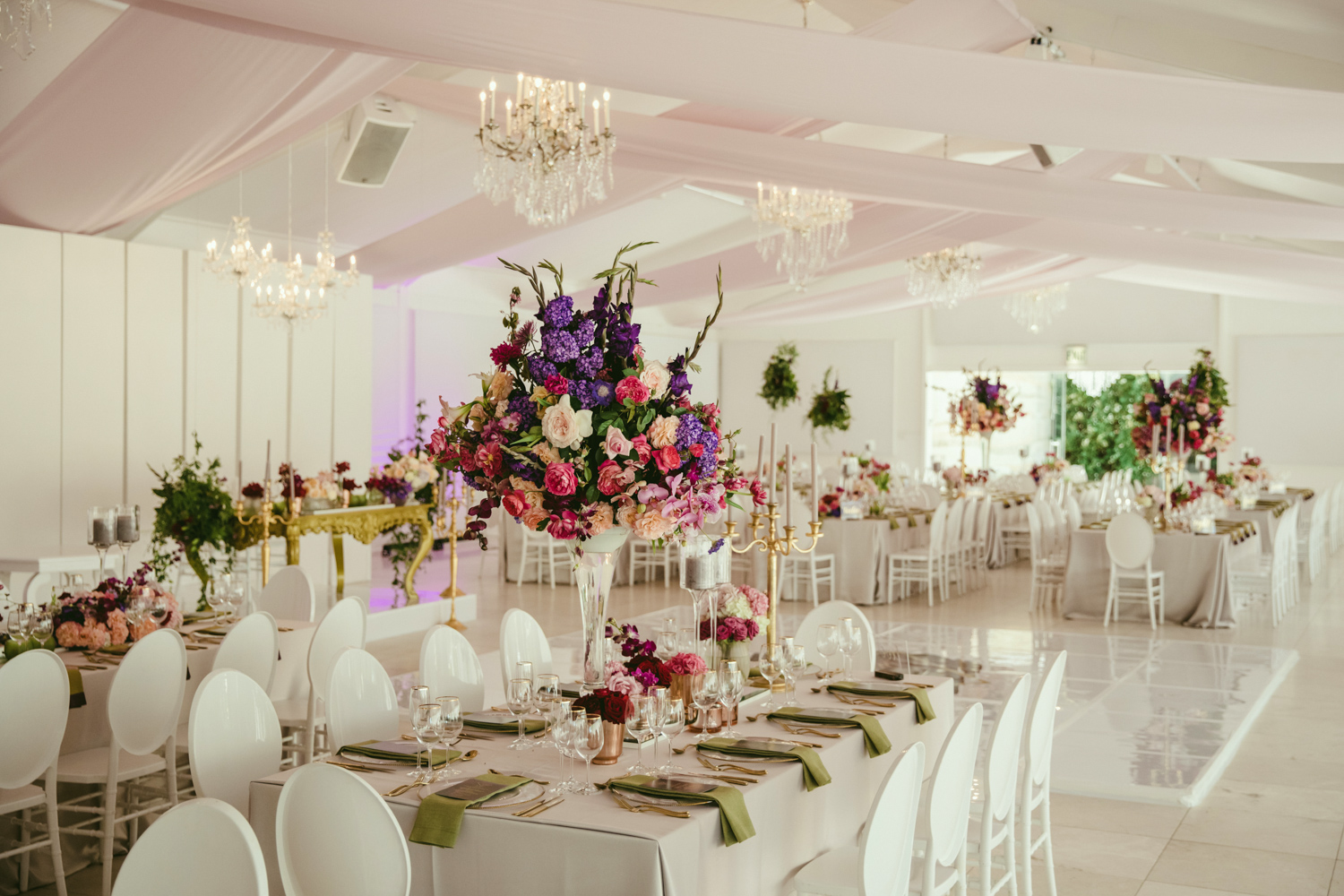 a decor shot in Laurent venue of small hanging greenery and pink floral arraignments on a mirror with gold cutlery and a golden rim under plate and white chairs.