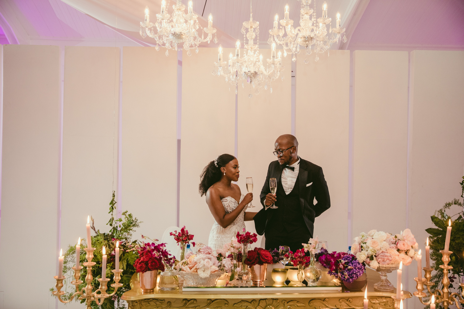 a bride and groom standing beside the bridal table drinking MCC in Laurent venue Lourensford.